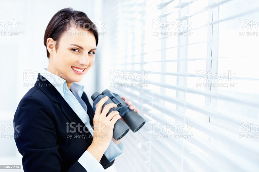 Happy business woman holding binoculars by window blinds royalty-free stock photo