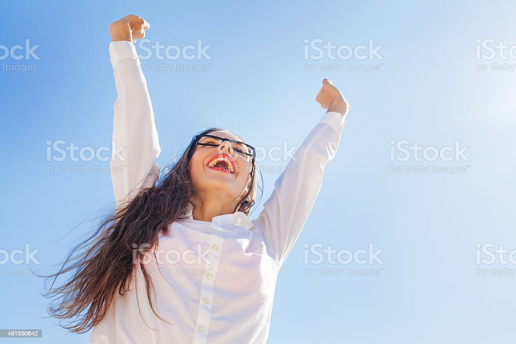happy business woman in a street with rised hands stock photo