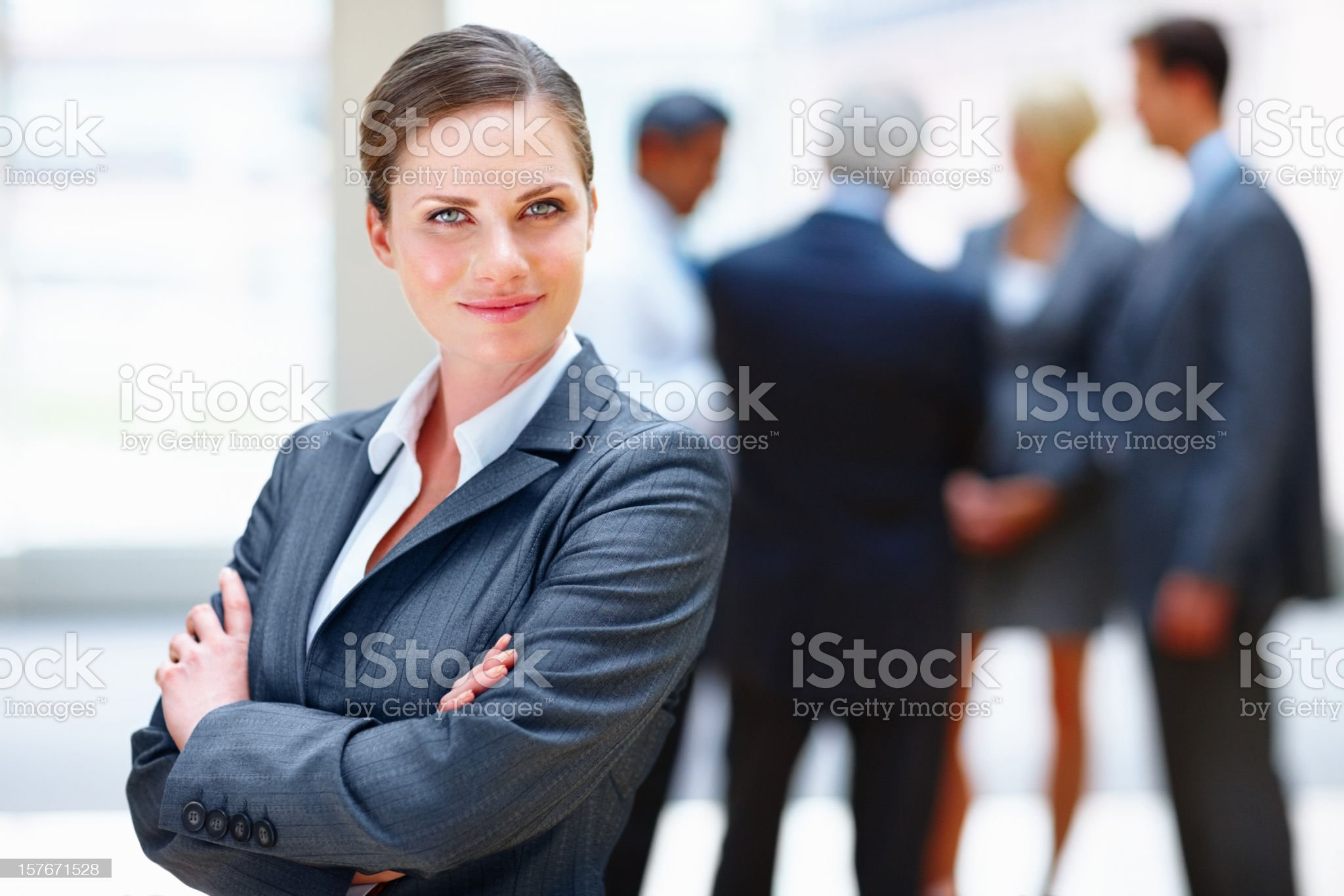 Happy business woman smiling with colleagues in the background royalty-free stock photo
