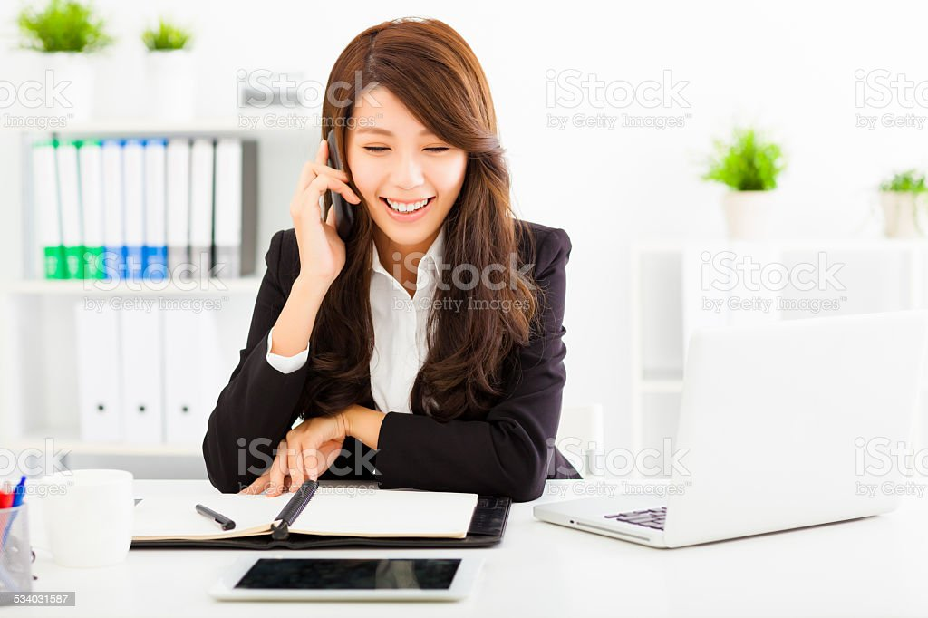 happy business woman talking on the phone in office stock photo