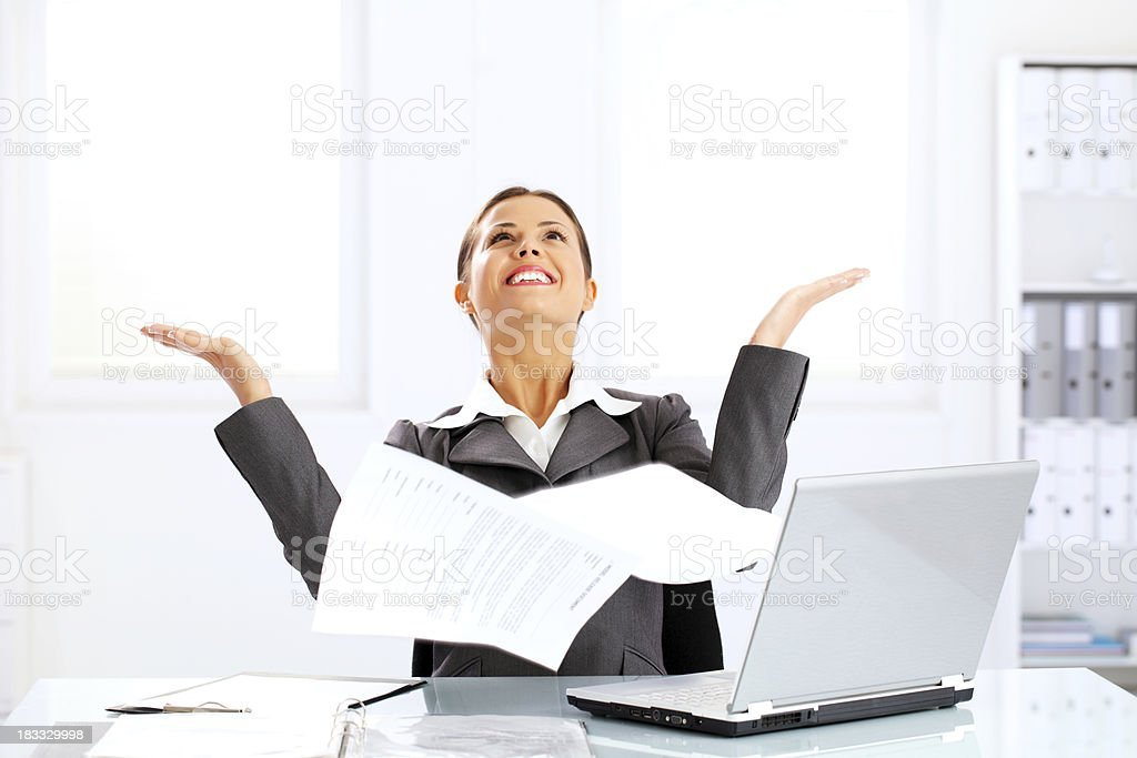 Happy business woman throwing papers in the air at office. royalty-free stock photo