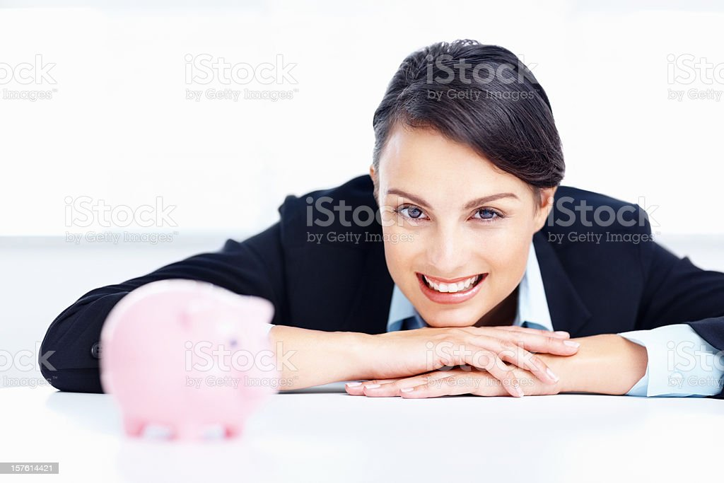 Happy business woman with a piggy bank at table royalty-free stock photo