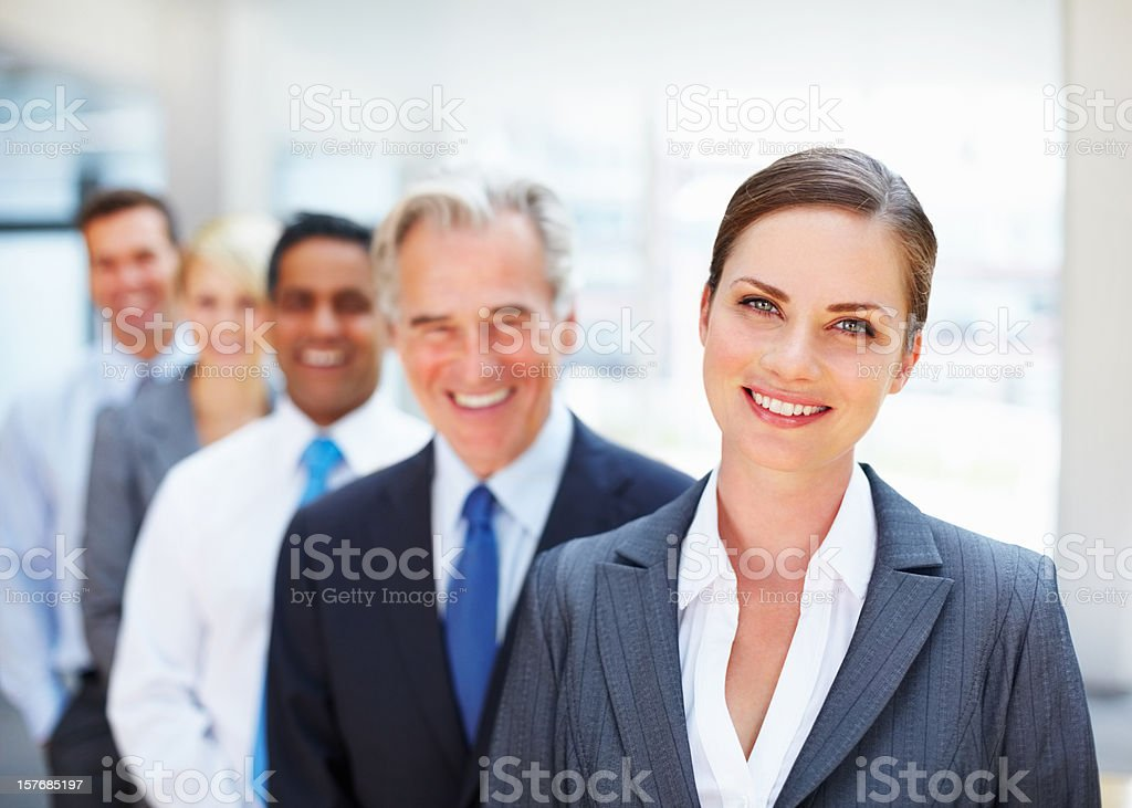 Happy business woman with colleagues standing in a row royalty-free stock photo
