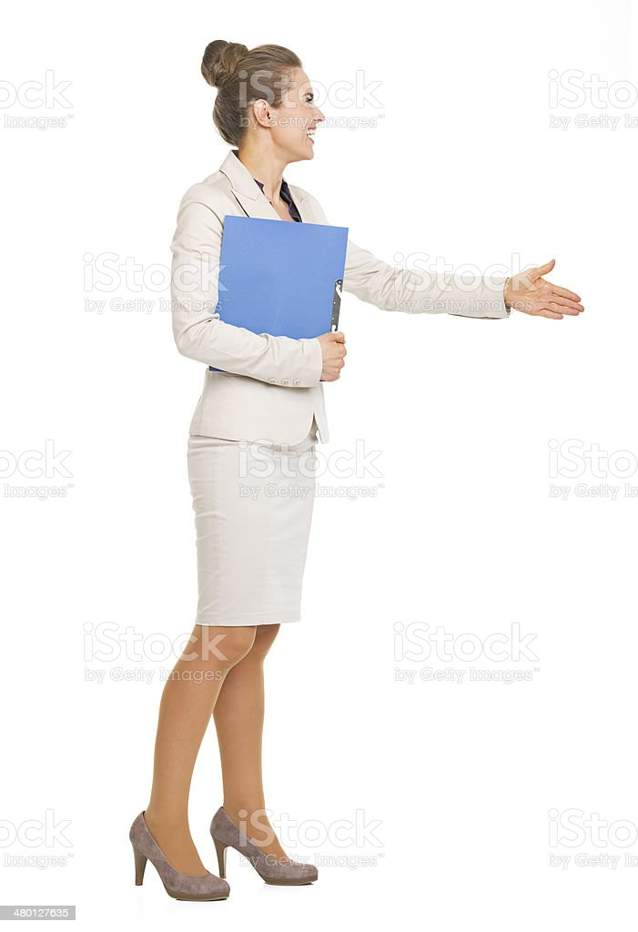 Happy business woman with folder stretching hand for handshake stock photo