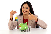 Happy business woman with stack of coins and piggy bank