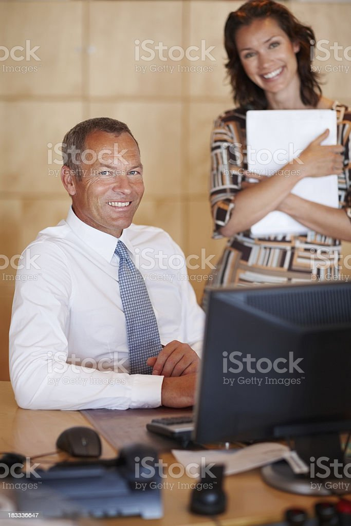 Happy businessman and secretary smiling at office desk royalty-free stock photo
