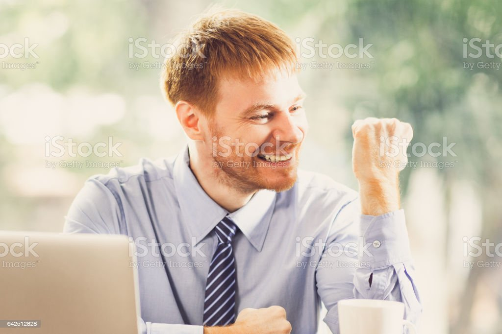 Happy Businessman Celebrating Success in Office stock photo