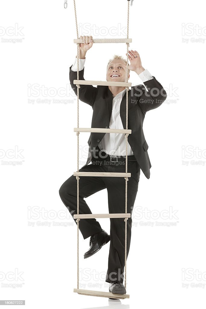 Happy businessman climbing a rope ladder stock photo