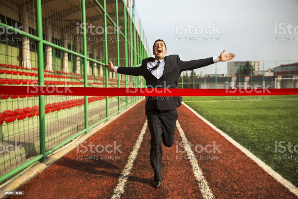 Happy businessman crossing the finishing line on a track stock photo