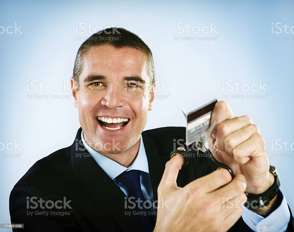 Happy businessman cutting up credit card -  is it his? royalty-free stock photo