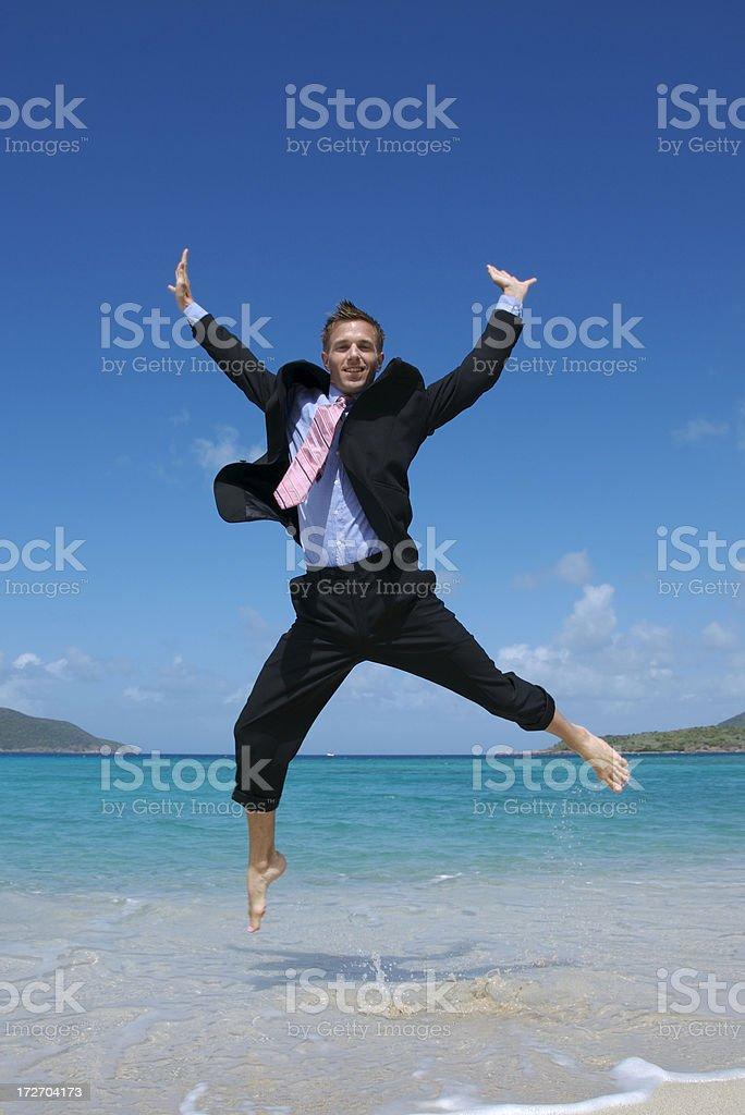 Happy Businessman Doing Spreadeagle Jump on Beach royalty-free stock photo