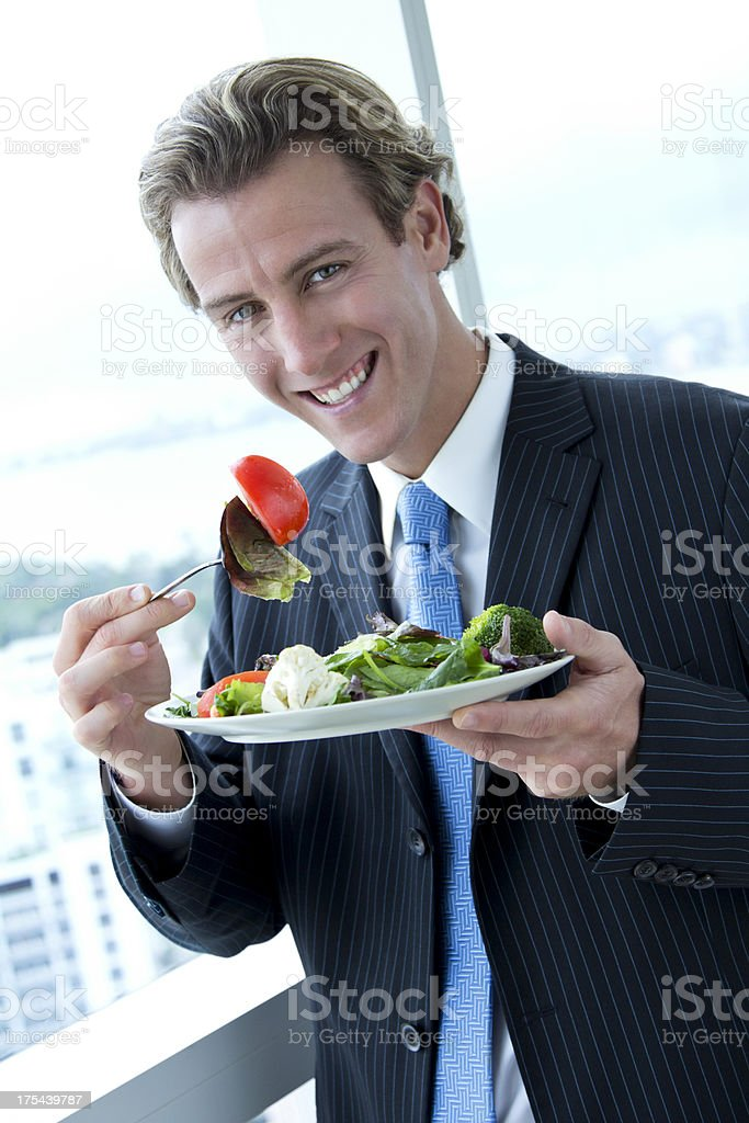 Happy businessman eating a salad stock photo