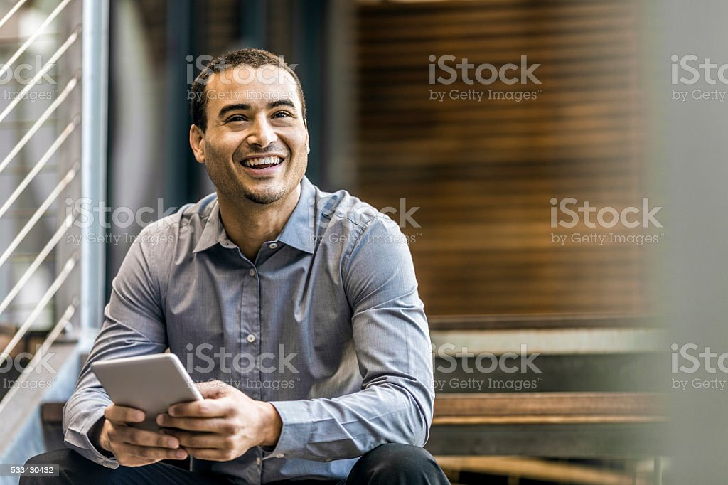 Happy businessman holding digital tablet stock photo