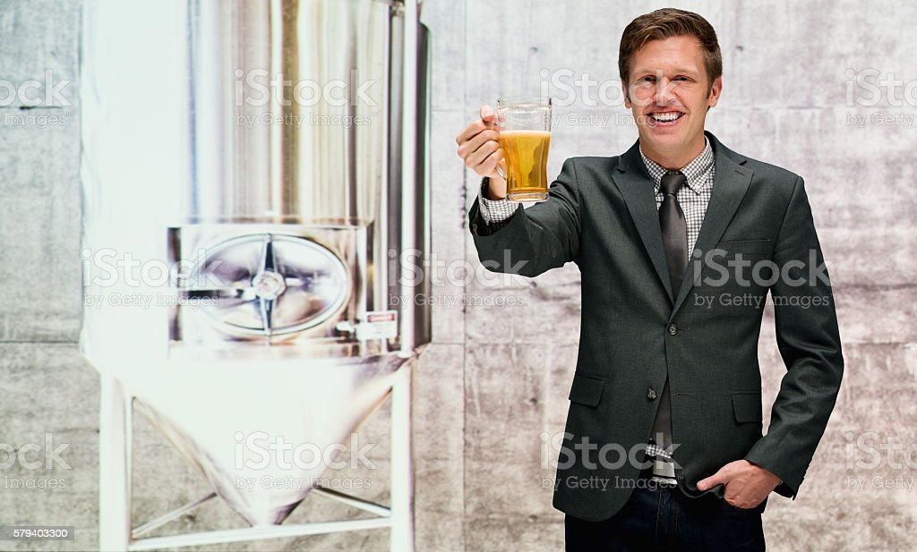 Happy businessman holding drinking glass in brewery stock photo