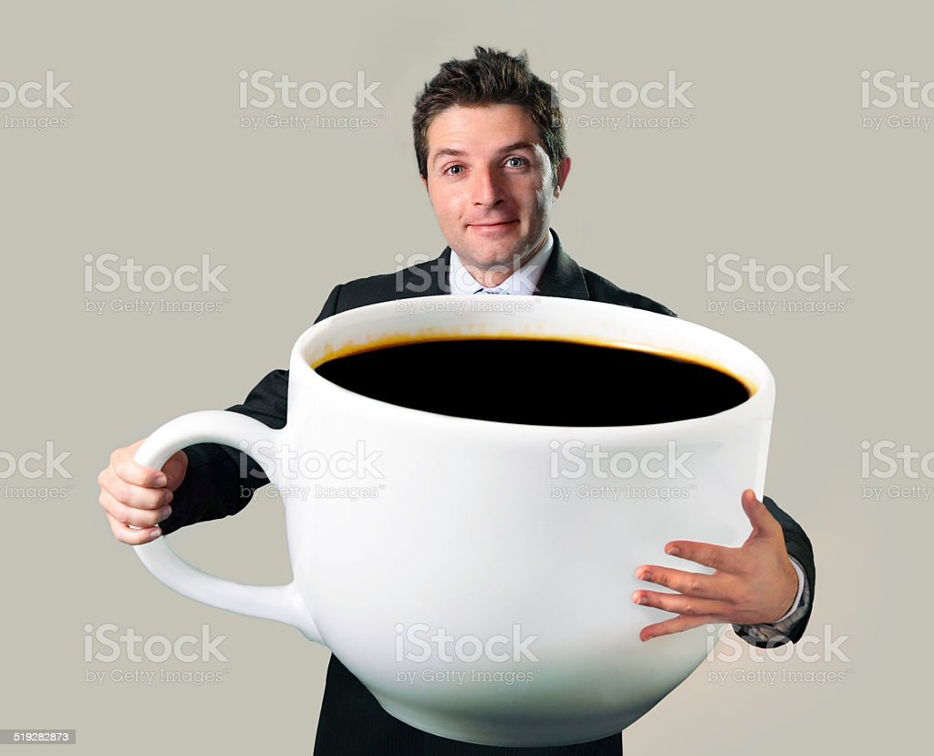 happy businessman holding funny huge  oversized cup of black cof stock photo