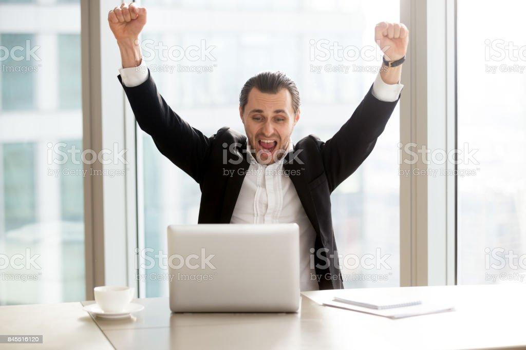 Happy businessman in front of laptop celebrating impressive achievement. stock photo