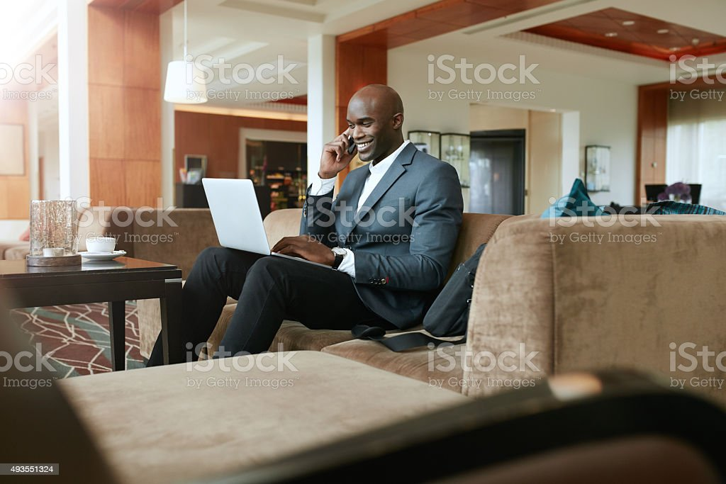Happy businessman in hotel lobby using cell phone and laptop stock photo