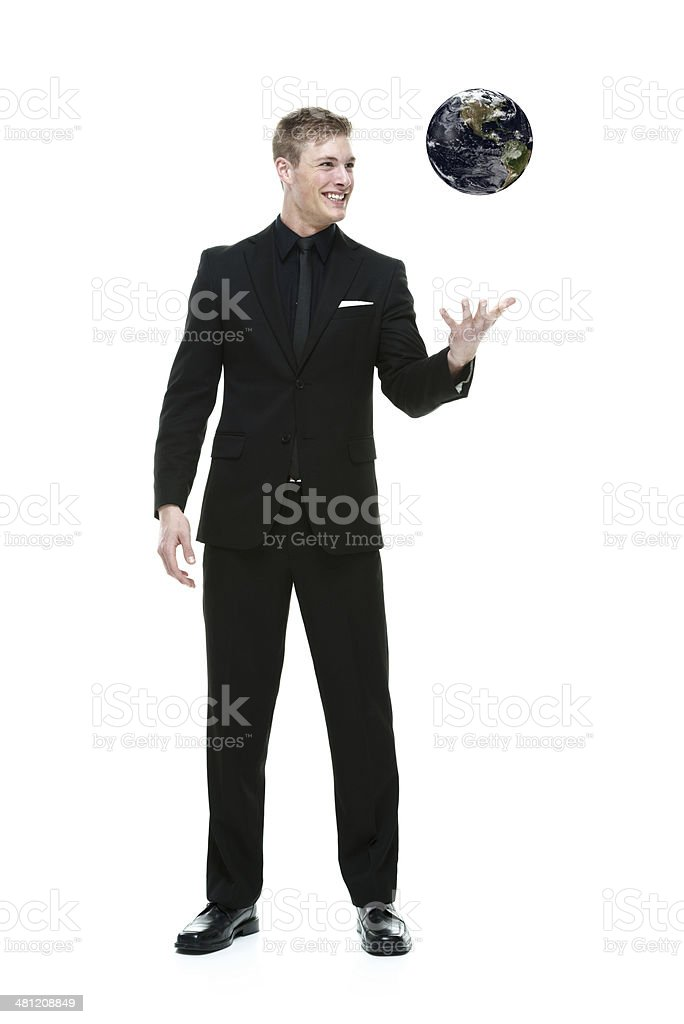 Happy businessman interacting with floating globe stock photo