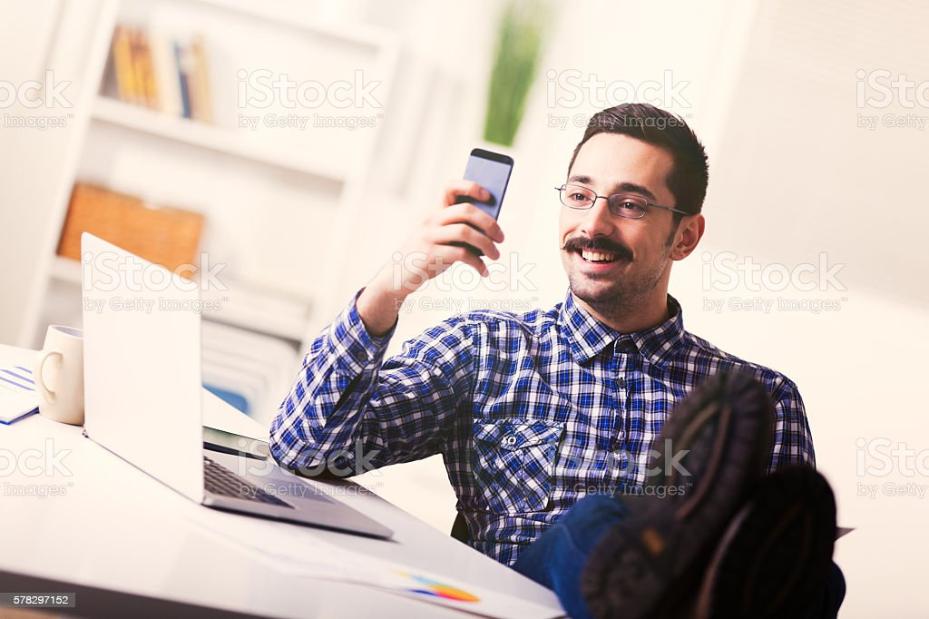 Happy businessman reading a text message on mobile phone stock photo