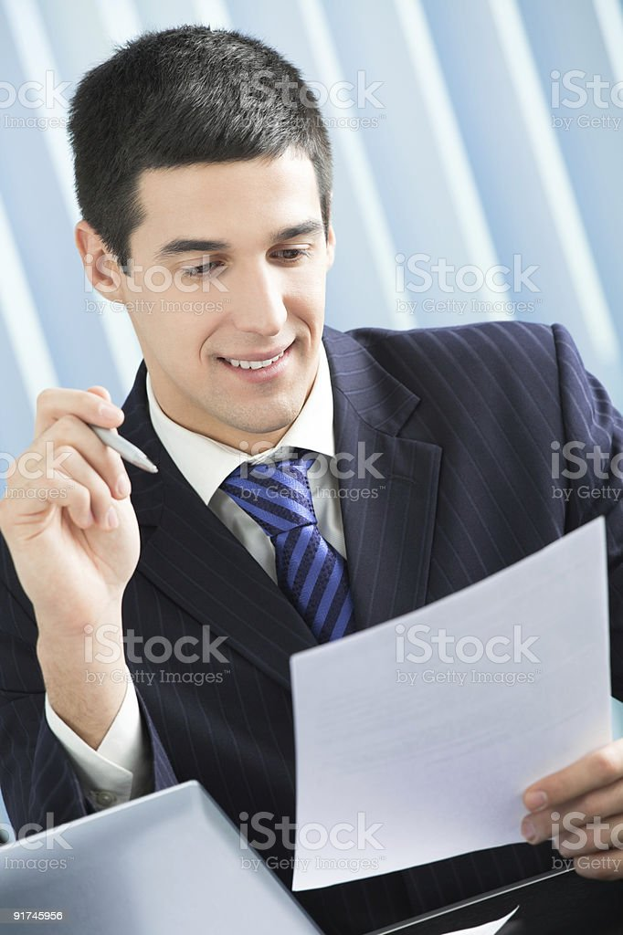Happy businessman reading document at office royalty-free stock photo