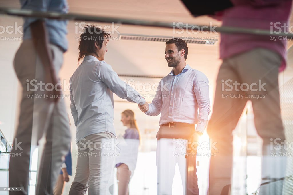 Happy businessman shaking hands with Japanese colleague in a hallway. stock photo