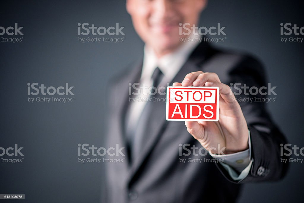 Happy Businessman showing  business card with Stop AIDS  sign stock photo