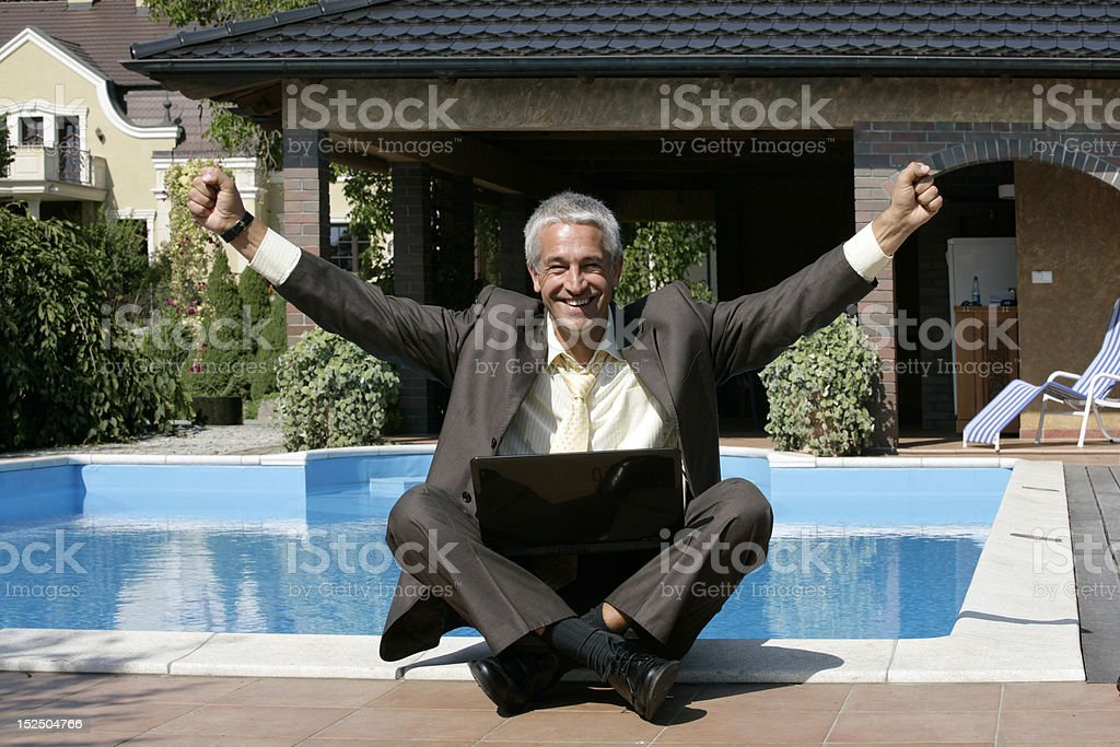 Happy businessman sitting next to the pool royalty-free stock photo
