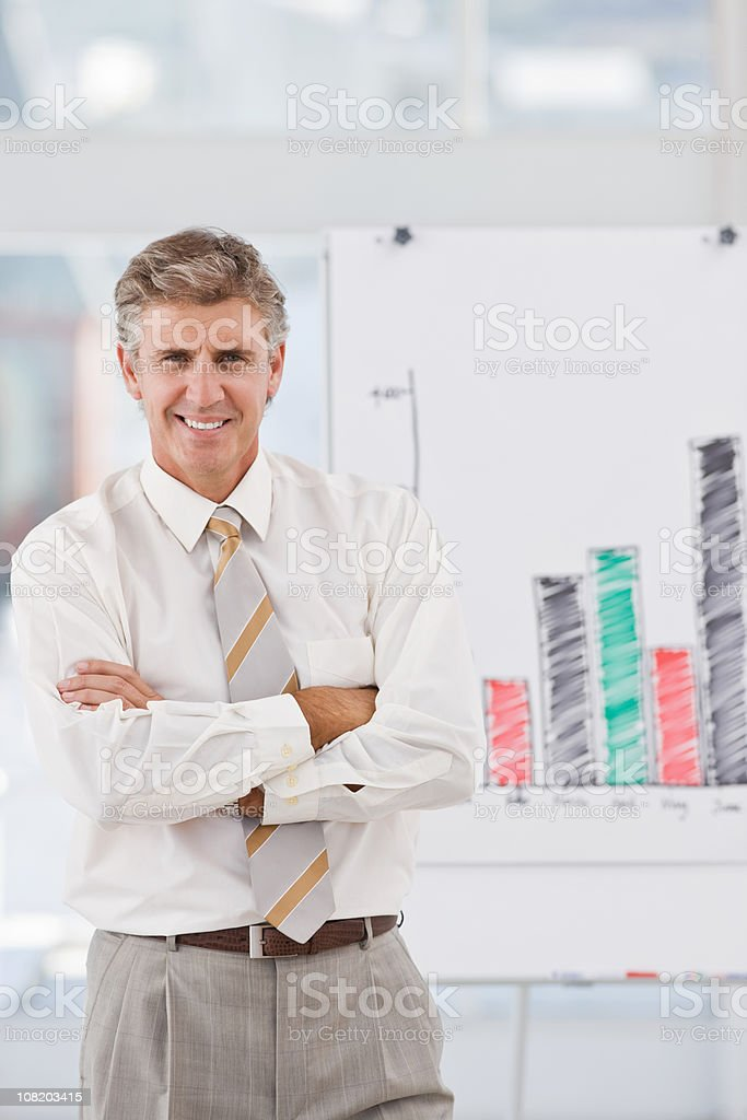 Happy businessman smiling beside graph royalty-free stock photo