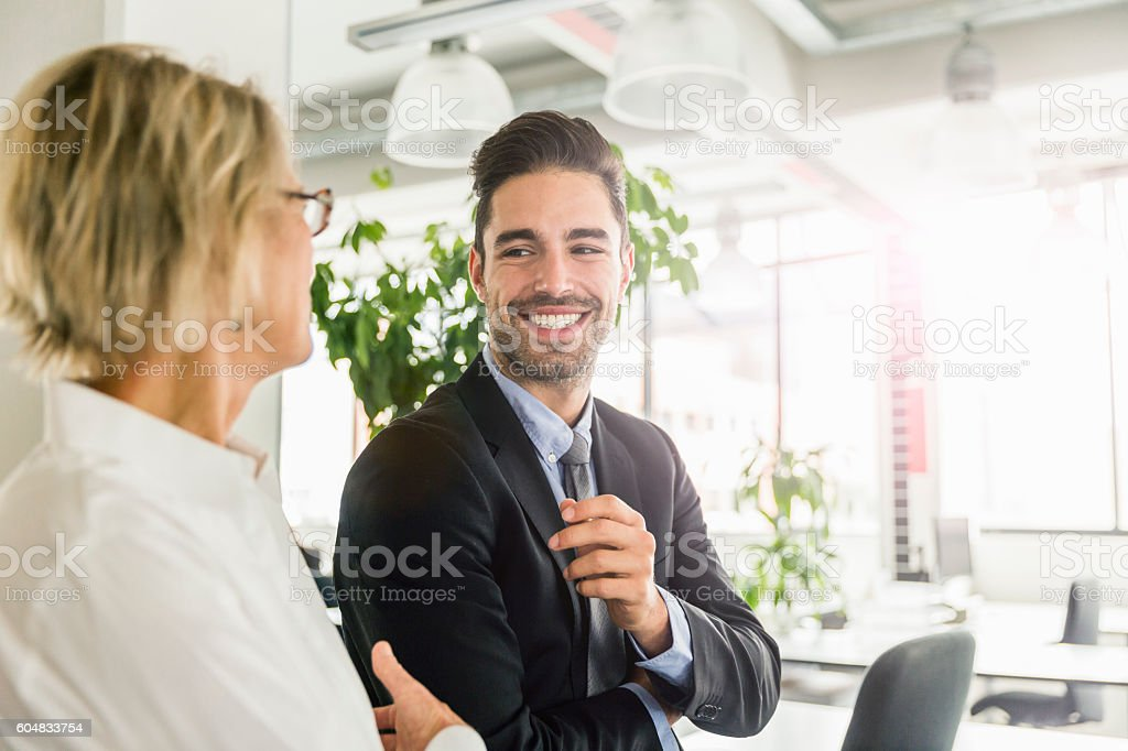 Happy businessman standing with coworker in office stock photo