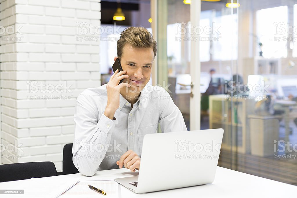 Happy businessman talking on the phone with his laptop royalty-free stock photo