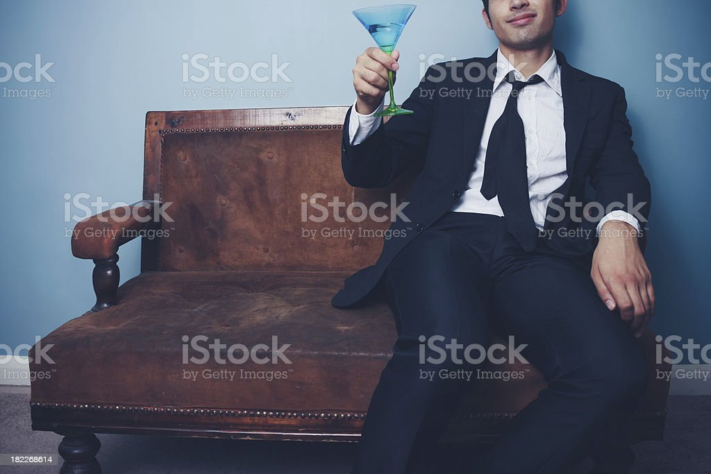 Happy businessman toasting while sitting on old couch royalty-free stock photo
