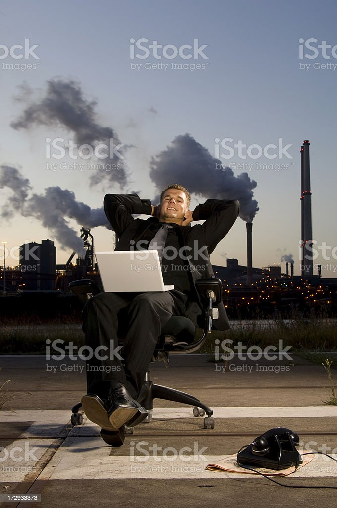 happy businessman using laptop in industrial environment royalty-free stock photo