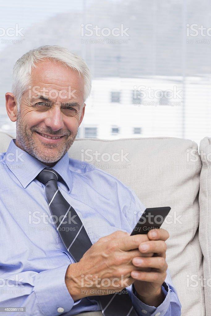 Happy businessman using smartphone royalty-free stock photo