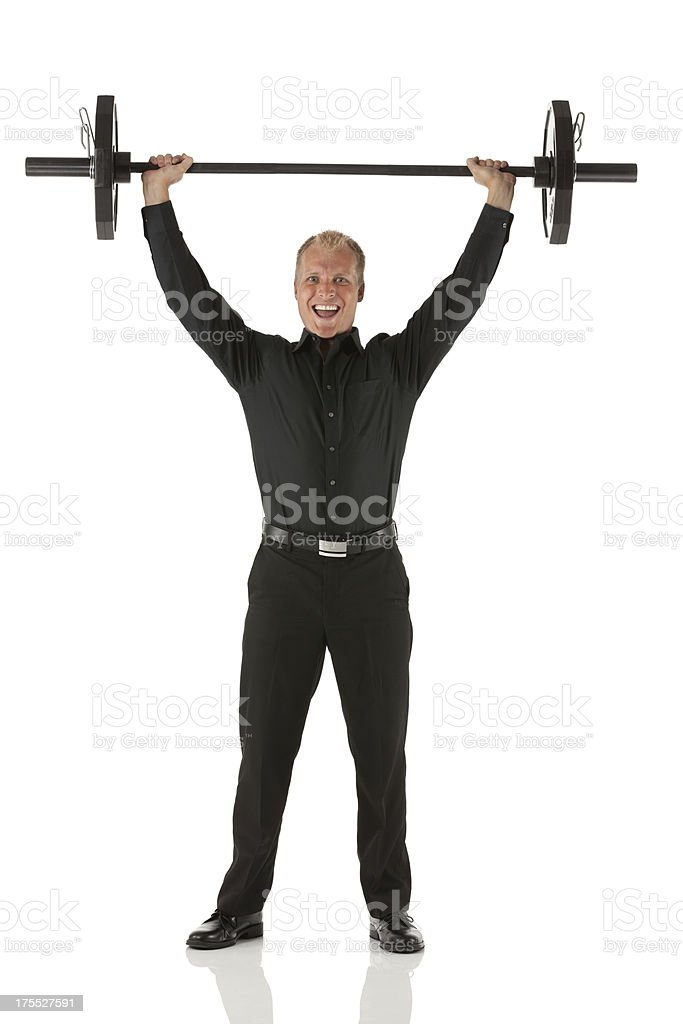 Happy businessman weightlifting stock photo