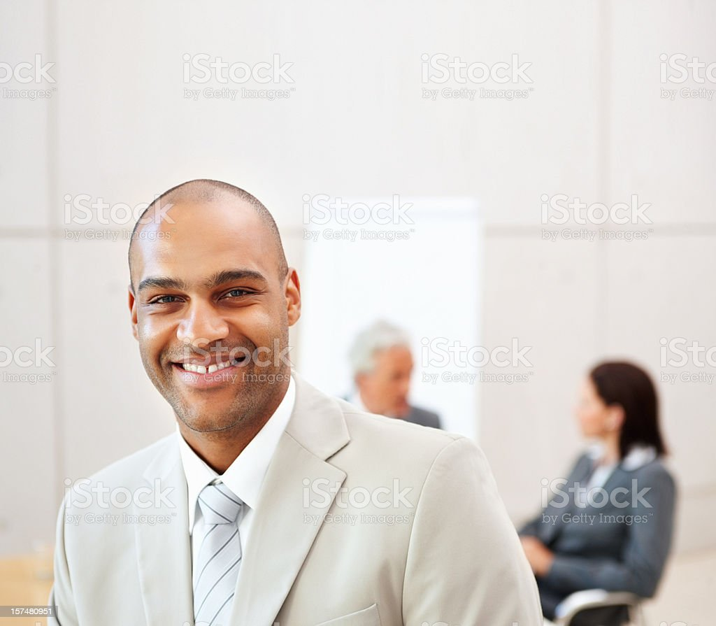 Happy businessman with colleagues in background royalty-free stock photo