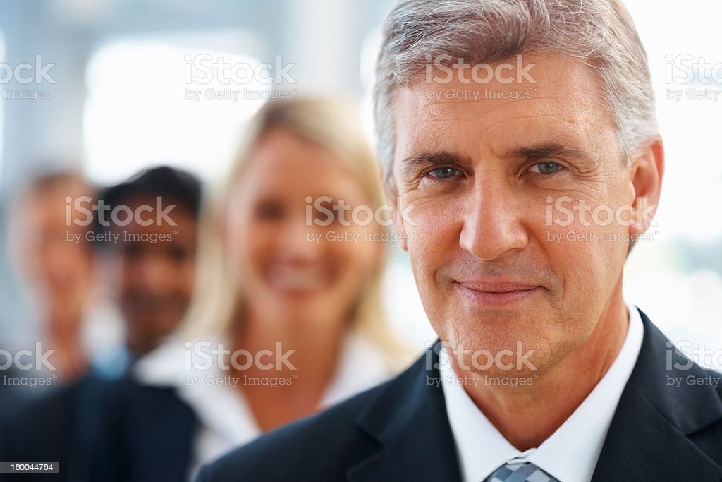 Happy businessman with colleagues in the background royalty-free stock photo
