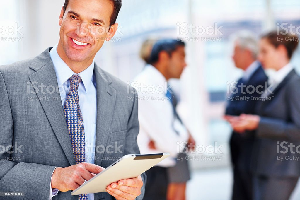 Happy businessman with executives discussing in the background royalty-free stock photo