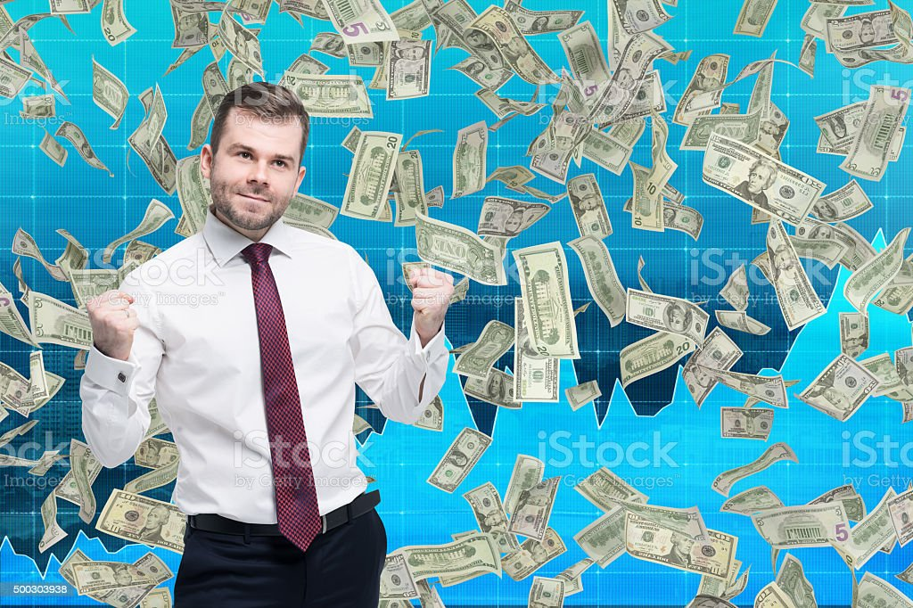 happy businessman with hands up, dollars falling from above stock photo