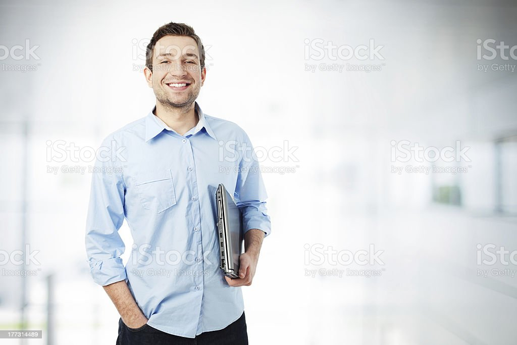 Happy businessman with laptop smiling stock photo