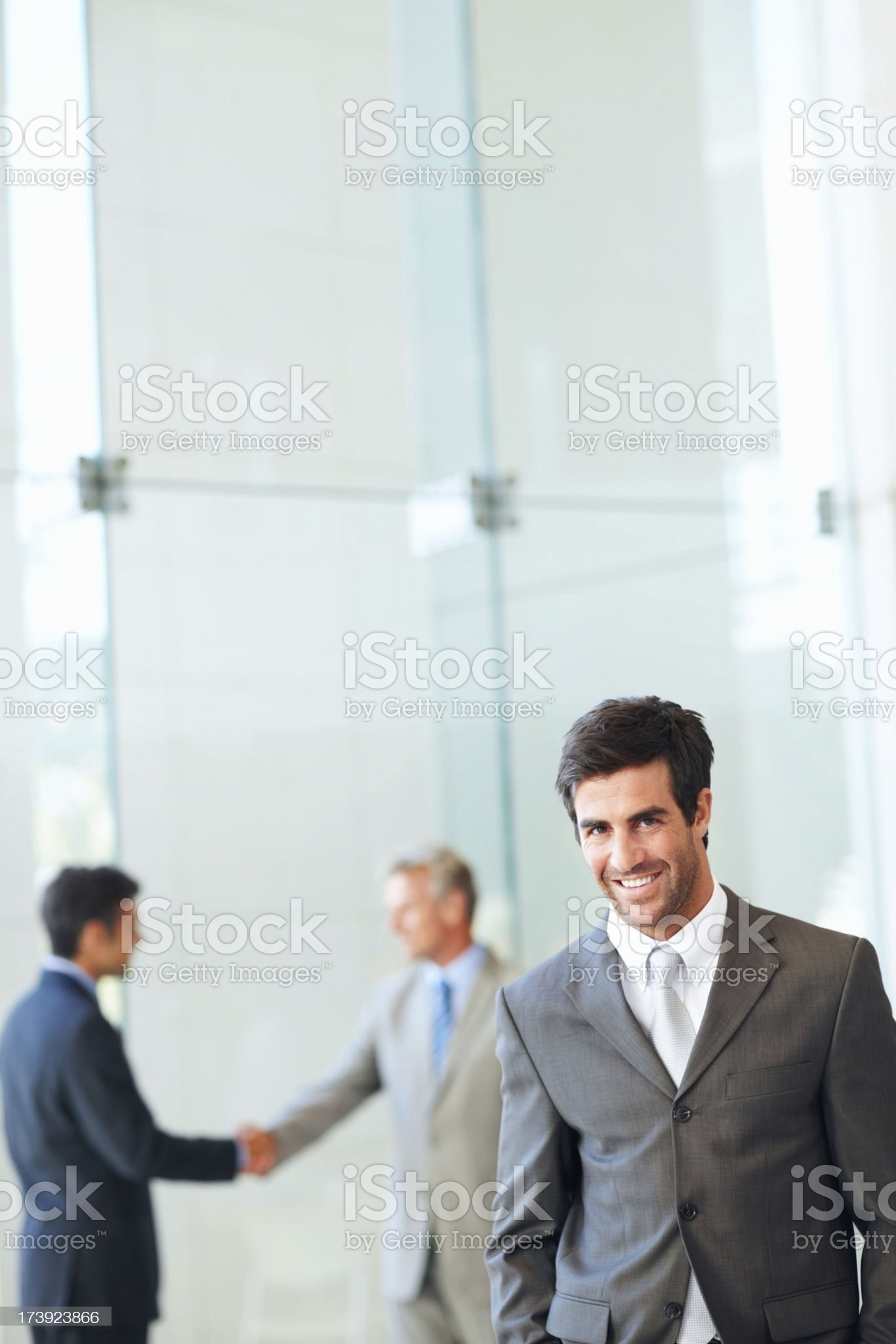 Happy businessman with people in background royalty-free stock photo