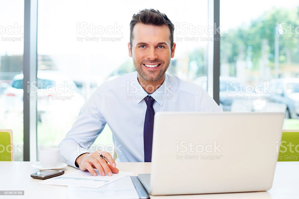 Happy businessman working at the office stock photo