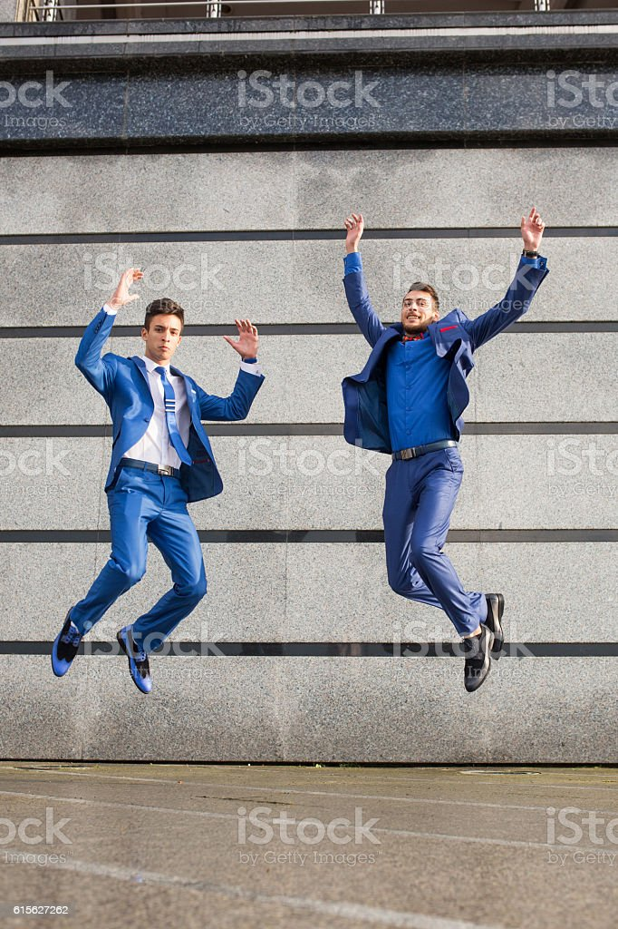 Happy businessmen jumping and celebrating their success. stock photo