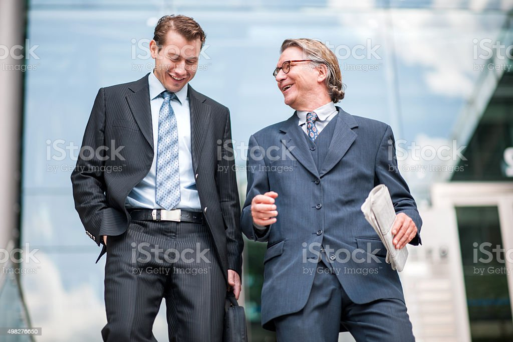 Happy businessmen walking outdoors and communicating. stock photo