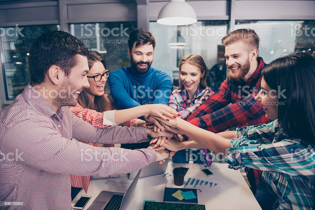 Happy businesspeople putting hands on top of hands stock photo