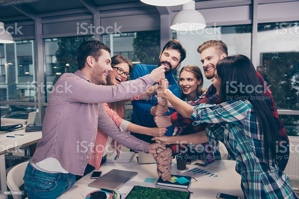 Happy businesspeople putting their fist on top of each other stock photo