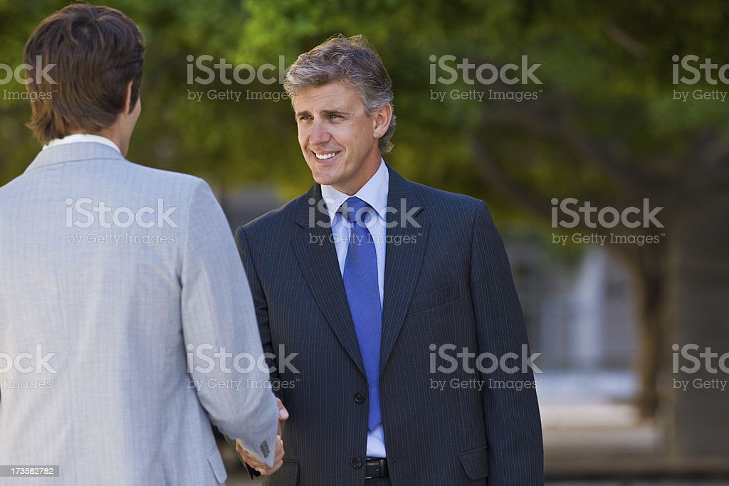 Happy businesspeople shaking hands together royalty-free stock photo