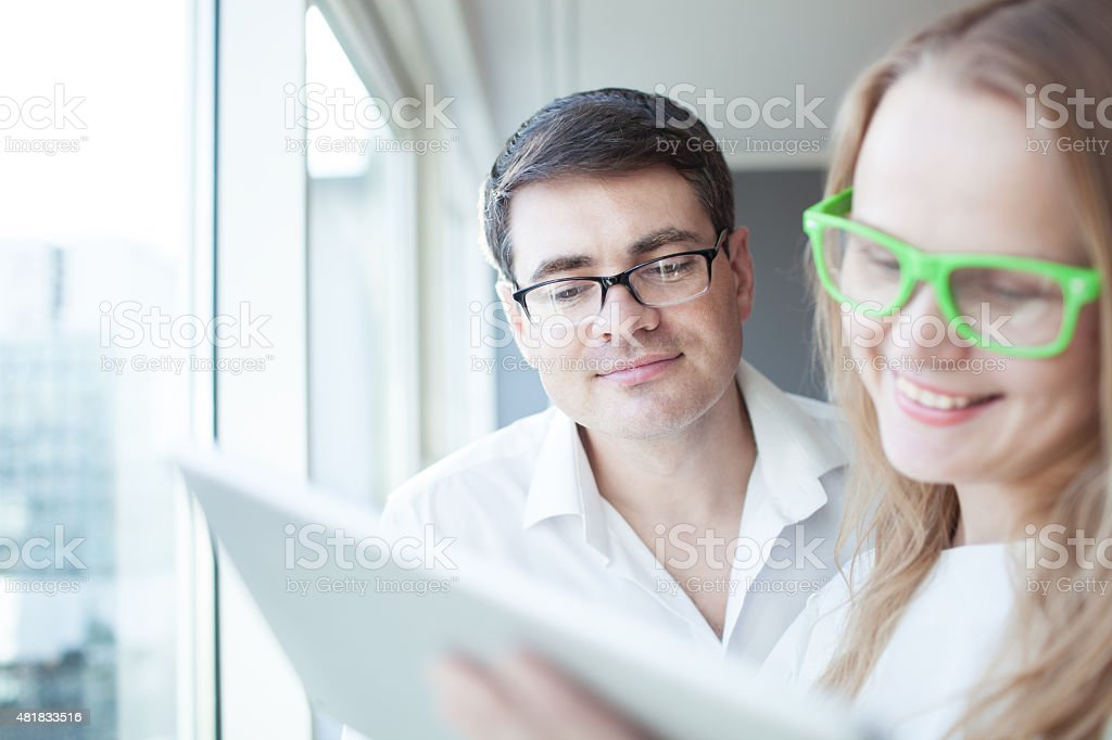 Happy businesspeople working with tablet PC in the office stock photo