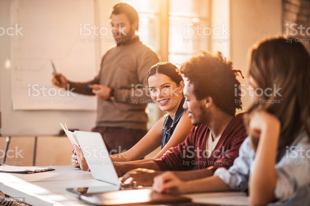 Happy businesswoman among her colleagues on a meeting. stock photo