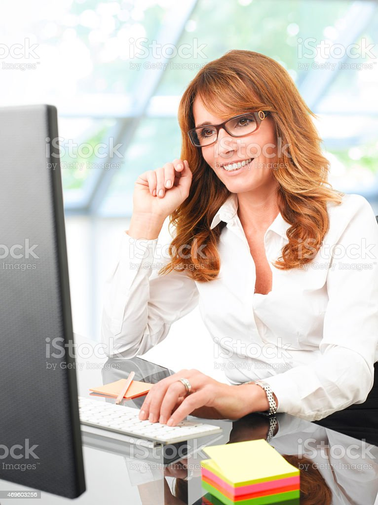 Happy businesswoman at office desk with a computer stock photo