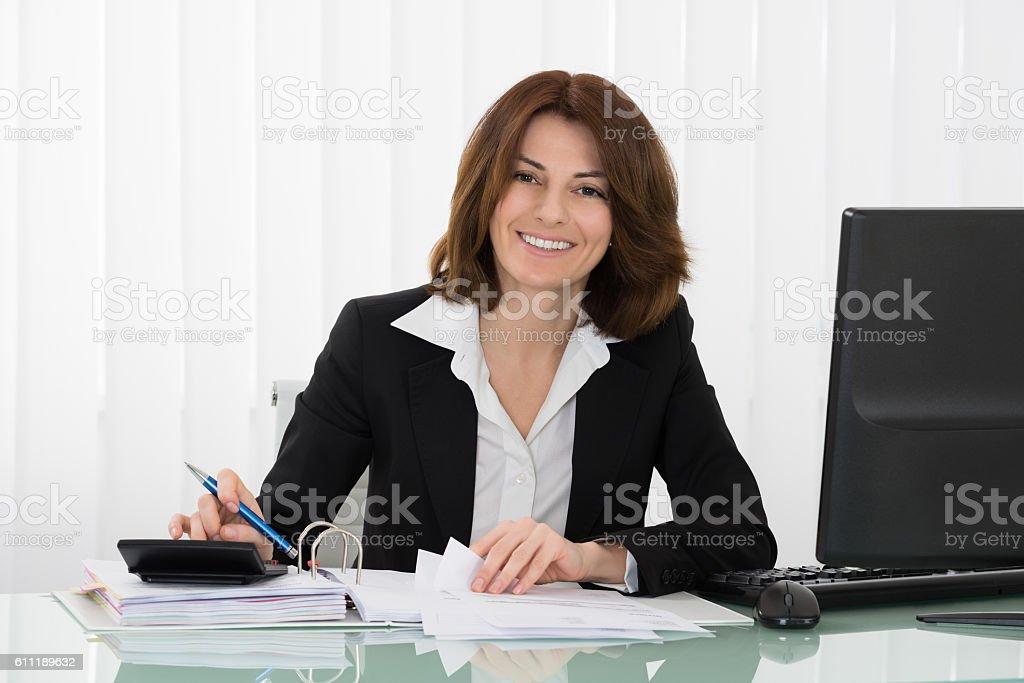 Happy Businesswoman Calculating Tax stock photo
